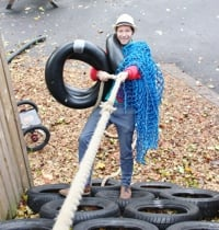 Ivan senior playworker and safety officer climbing tyre wall
