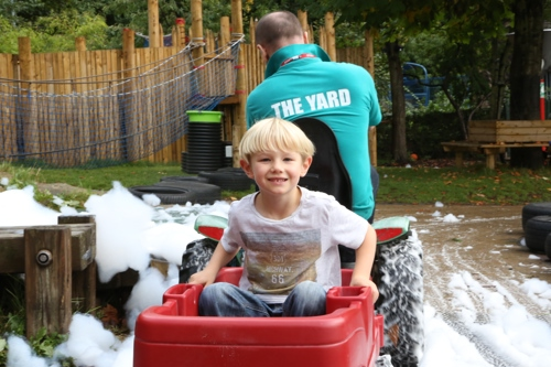 blonde boy in trailer being driven round track with bubbles by adult in The Yard tshirt