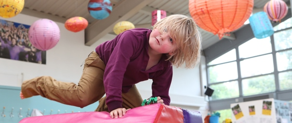young child balancing on soft play block with lanterns in background