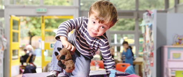 young boy with teddy climbing on soft play