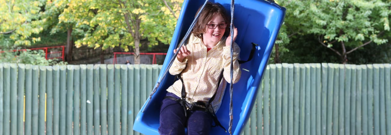 girl wearing glasses swinging on blue bucket seat swing in front of wooden fence